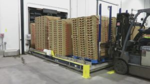 A forklift unloads strawberry pallets from a MACS precooler